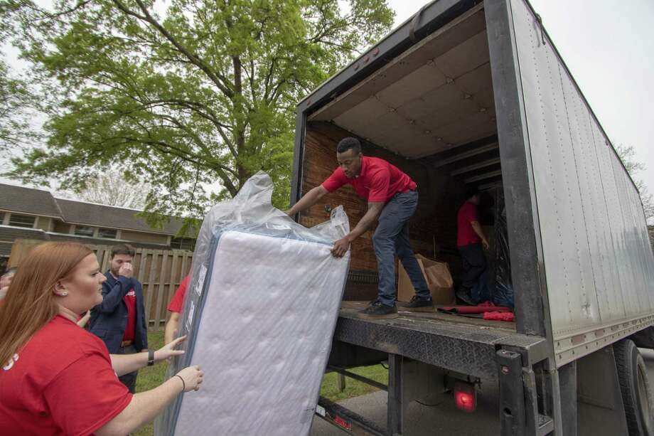 Ray Miyares with Mattress Firm passes a mattress to Brittany Bivens on Tuesday, March 12, 2019 at the Treehouse Center in Conroe. Mattress Firm donated 25 mattresses to the center. Photo: Cody Bahn, Houston Chronicle / Staff Photographer / © 2018 Houston Chronicle