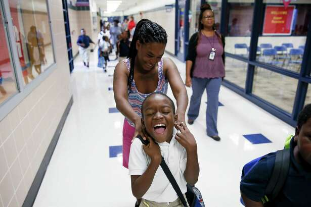 In this August 2018 file photo, Jontreal Jenkins, 8, laughs as his mother, Alicia Jenkins, tickles him as she walks him to his second grade class for the first day of school as students return to Hilliard Elementary School for the first time since Hurricane Harvey.