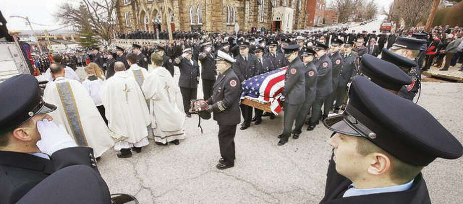 "The helmet of Godfrey Fire Capt. Jacob ""Jake"" Ringering is carried ahead of his flag-draped casket as he is carried Tuesday from funeral services at St. Mary's Catholic Church and to a waiting Godfrey fire truck. Ringering was killed last week while fighting a house fire near Bethalto. Hundreds of firefighters and police officers from across the region turned out to honor Ringering in a large traditional firefighters funeral. Photo: John Badman 
