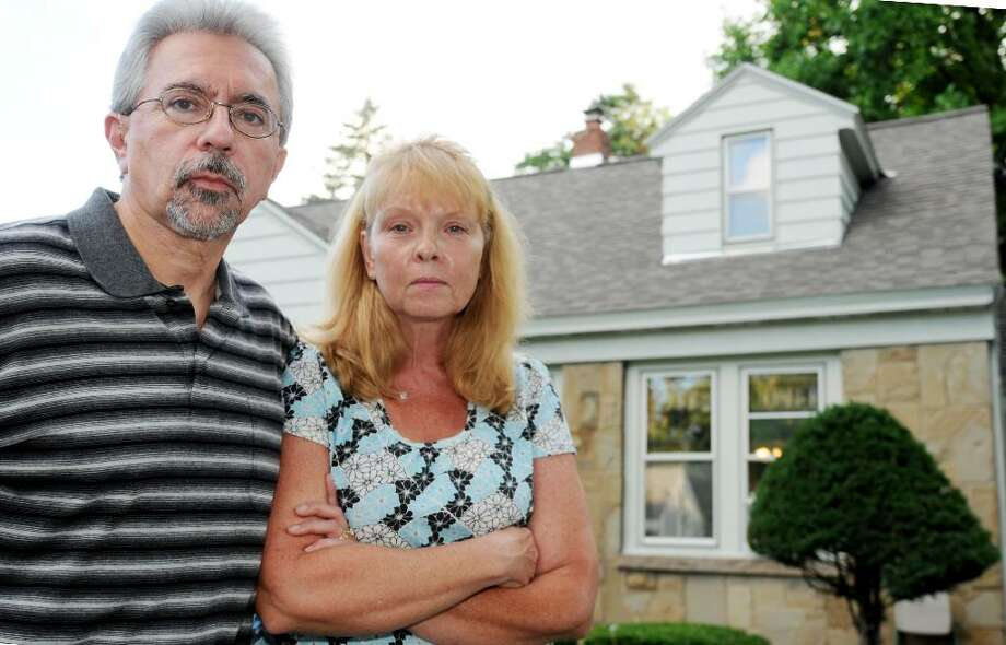 Victor & Kimberly Martini outside their home in Rotterdam, NY, on Wednesday, July 21, 2010. They are seeking compensation from a contractor who installed a 2004 roof, which they say was leaky, for the more-than $6,000 cost of this satisfactory replacement roof. (Luanne M. Ferris / Times Union) Photo: LMF
