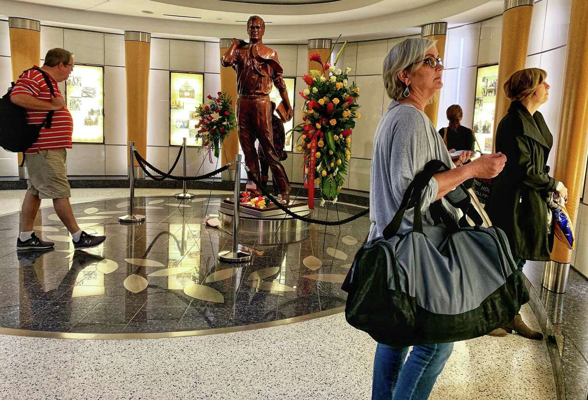 Travelers stop to pay their respects to former President George H.W. Bush at his statue in Terminal C at George Bush Intercontinental Airport on Sunday, December 2, 2018. Bush, 94, passed away at his Houston home on November 30, 2018.
