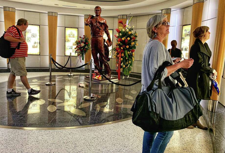 Travelers stop to pay their respects to former President George H.W. Bush at his statue in Terminal C at George Bush Intercontinental Airport on Sunday, December 2, 2018. Bush, 94, passed away at his Houston home on November 30, 2018. Photo: Jill Karnicki, Houston Chronicle / Staff Photographer / © 2018 Mark Mulligan / Houston Chronicle