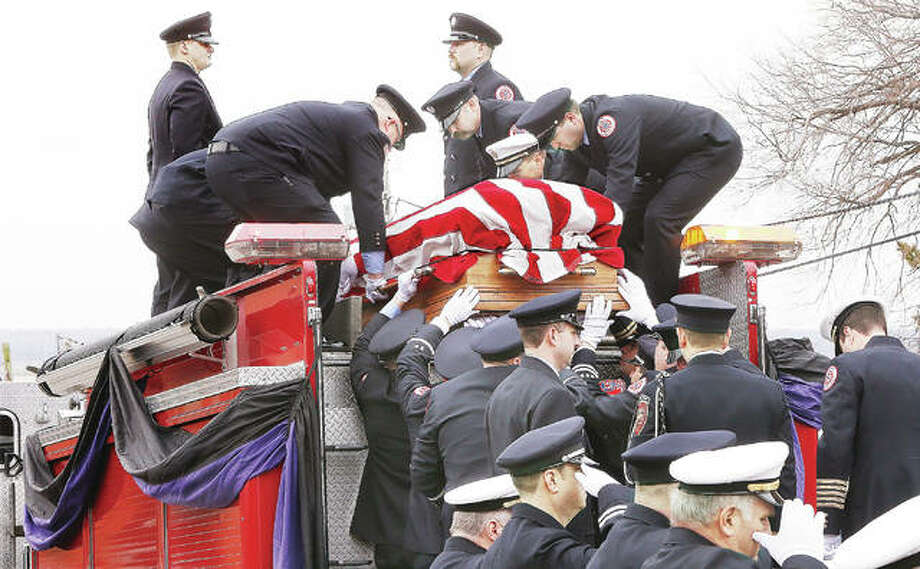 "Firefighters load the flag draped casket of Godfrey Fire Capt. Jacob ""Jake"" Ringering, 37, onto the back of a Godfrey fire truck Tuesday outside St. Mary's Catholic Church for the trip to Valhalla Memorial Park in Godfrey for burial. Ringering was killed last week while fighting a house fire near Bethalto. Hundreds of firefighters from across the region and state participated in the funeral and procession. Photo: John Badman 