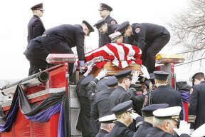 "Firefighters load the flag draped casket of Godfrey Fire Capt. Jacob ""Jake"" Ringering, 37, onto the back of a Godfrey fire truck Tuesday outside St. Mary's Catholic Church for the trip to Valhalla Memorial Park in Godfrey for burial. Ringering was killed last week while fighting a house fire near Bethalto. Hundreds of firefighters from across the region and state participated in the funeral and procession."