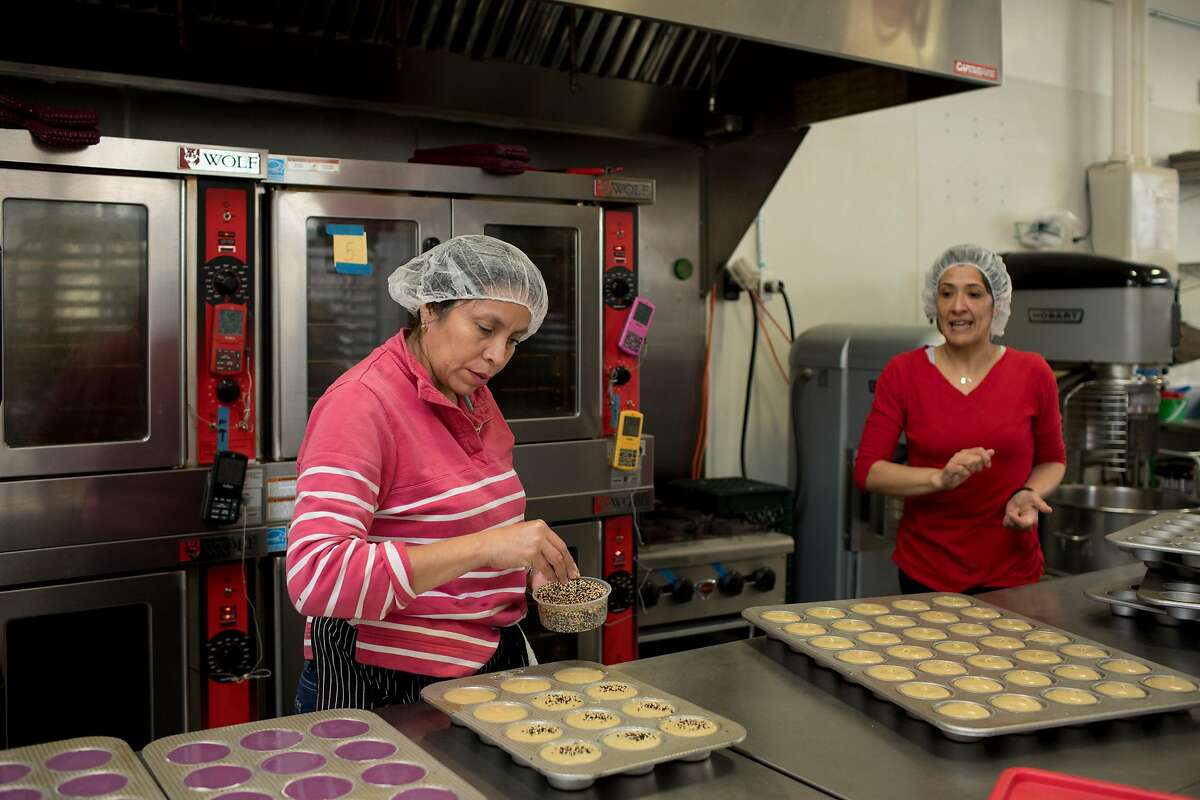 Teresa Luna (left) sprinkles black and white sesame seeds on top of mochi muffin batter while kitchen manager Diana Sanchez (right) looks on at Third Culture Bakery in Berkeley, Calif. on Sunday, January 27, 2019.