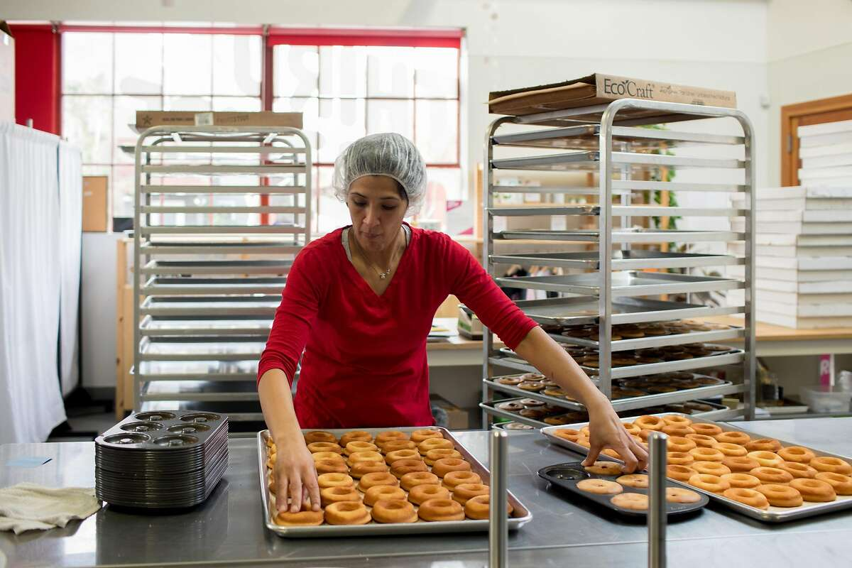 Kitchen manager Diana Sanchez removes baked mochi donuts from pans at Third Culture Bakery in Berkeley, Calif. on Sunday, January 27, 2019.