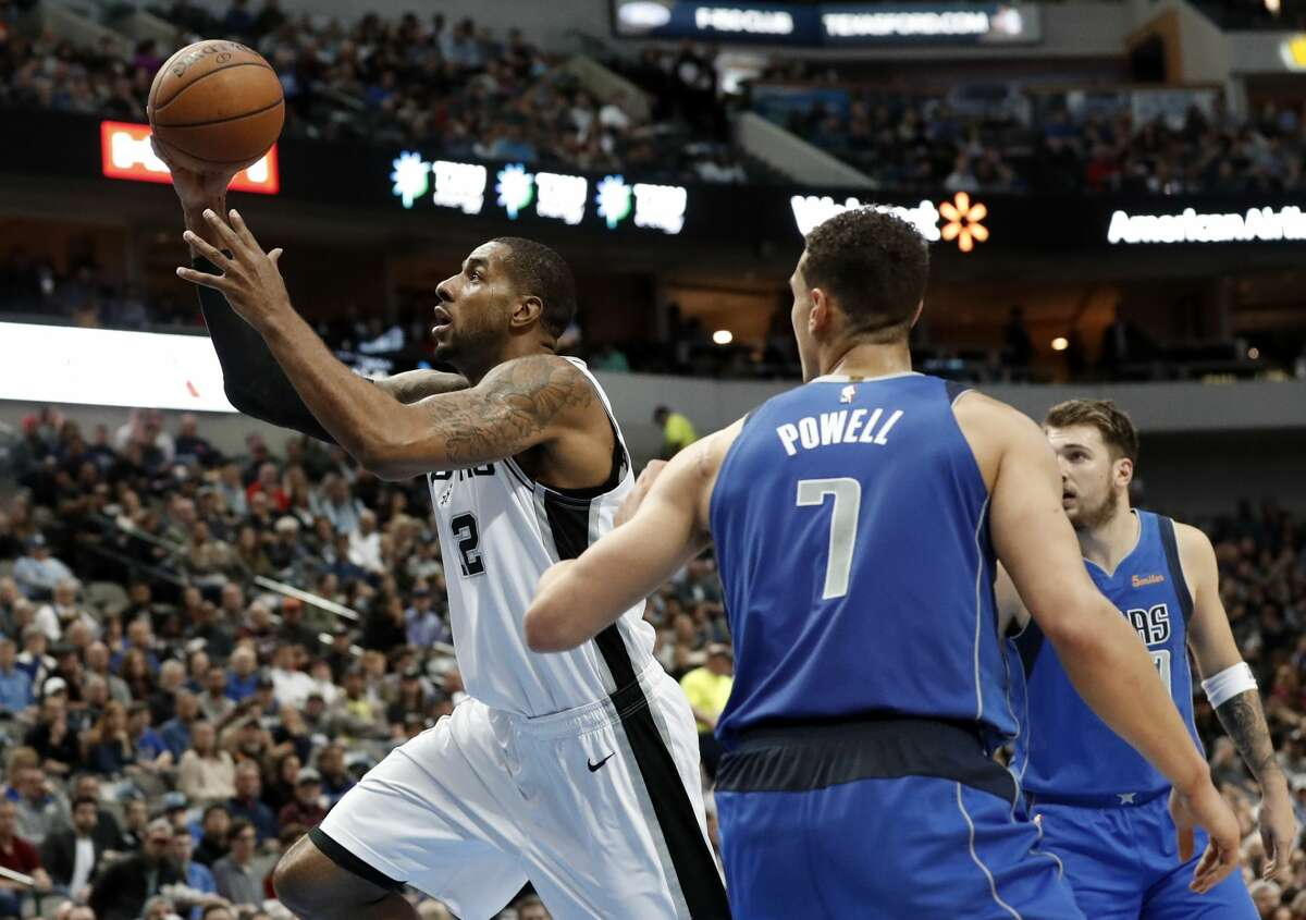 San Antonio Spurs center LaMarcus Aldridge (12) gets past Dallas Mavericks forward Dwight Powell (7) and Luka Doncic, rear, for a shot during the first half of an NBA basketball game in Dallas, Tuesday, March 12, 2019. (AP Photo/Tony Gutierrez)