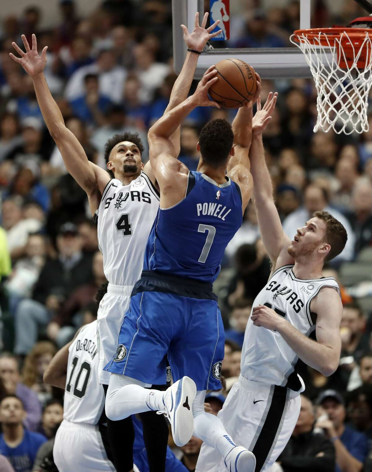 Dallas Mavericks forward Dwight Powell (7) goes up for a shot as San Antonio Spurs' DeMar DeRozan (10), Derrick White (4) and Jakob Poeltl, right, defend during the first half of an NBA basketball game in Dallas, Tuesday, March 12, 2019. (AP Photo/Tony Gutierrez)
