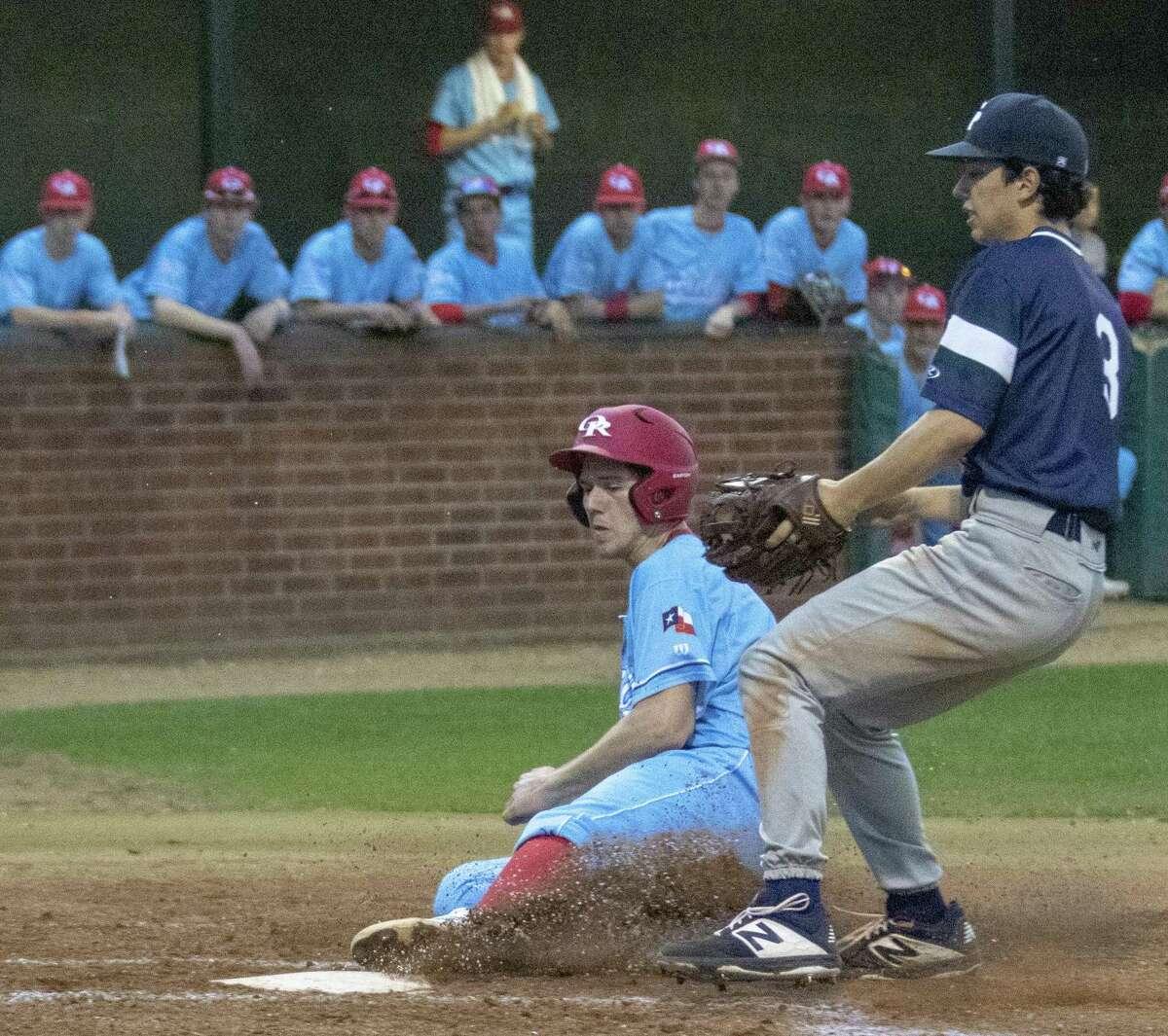Oak Ridge first baseman Kevin Skweres (23) slides into home plate during a District 15-6A baseball game at Oak Ridge High School.