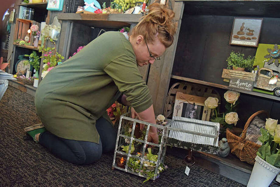 Primrose & Lace manager Shayla Allen fills a lantern Tuesday with greenery, candles and decorative birds to create a springtime arrangement. Photo: Nick Draper | Journal-Courier