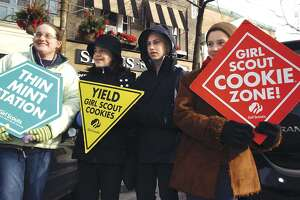 Members of Greenwich Girl Scout Troup 348 stop Greenwich Avenue traffic on Jan. 25, 2004, with their signs advertising Girl Scout cookies, which they were selling in front of Shoes N'More.