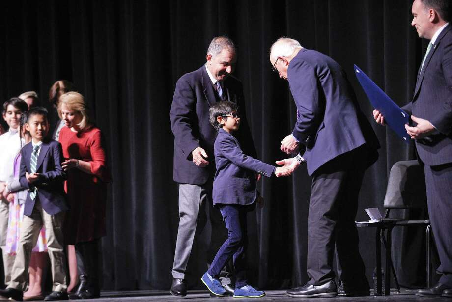 Hamilton Avenue School second-grader John Tembeck shakes the hand of Ernest Fleishman after being recognized during the annual Community Service Awards Ceremony held at Greenwich High School's Performing Arts Center in Greenwich, Conn. on Tuesday, March 12, 2019. Tembeck was among 26 fellow students recognized for participation in service activities that help improve both their school and community. Photo: Matthew Brown / Hearst Connecticut Media / Stamford Advocate