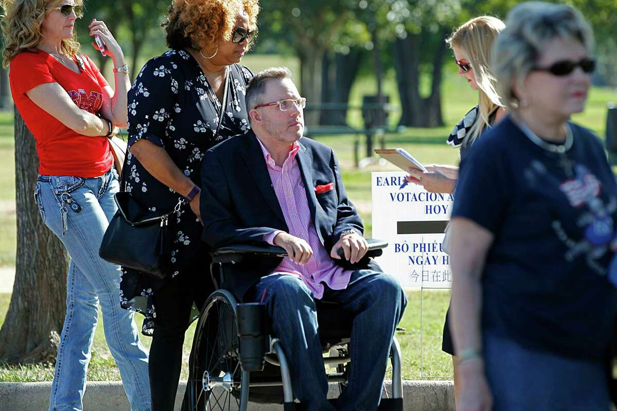 Toby Cole center, waits in line to vote at Nottingham Park with his personal assistant Contessa Carr and his girl friend Amanda Gonzales second from right, Oct. 28, 2016, in Houston.
