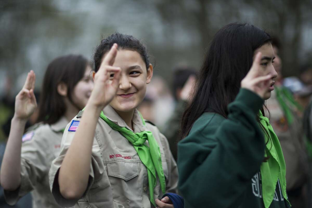 Troop 1314 member Madeline Gaiser, center, 13, holds up three fingers, a gesture long used in Boy Scouts, during the opening ceremony at Camporee.