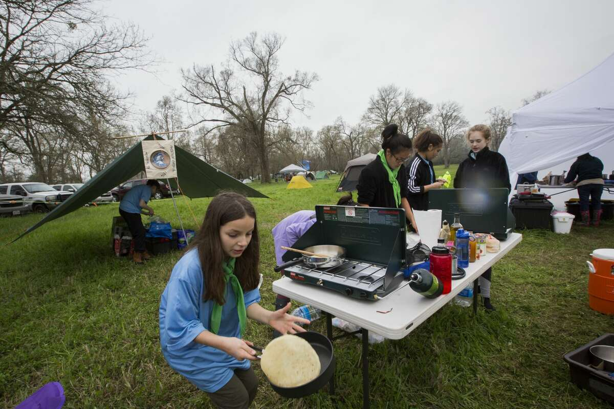 Christina McClelland, 10, the youngest member of Troop 1314, saves a tortilla from falling off her skillet while cooking dinner for her patrol.