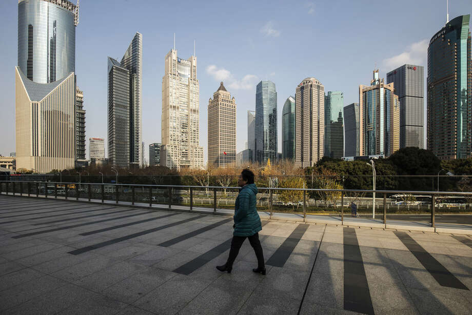 A pedestrian walks on an elevated walkway past buildings in Pudong's Lujiazui Financial District in Shanghai on Dec. 28, 2018. Photo: Bloomberg Photo By Qilai Shen. / © 2018 Bloomberg Finance LP