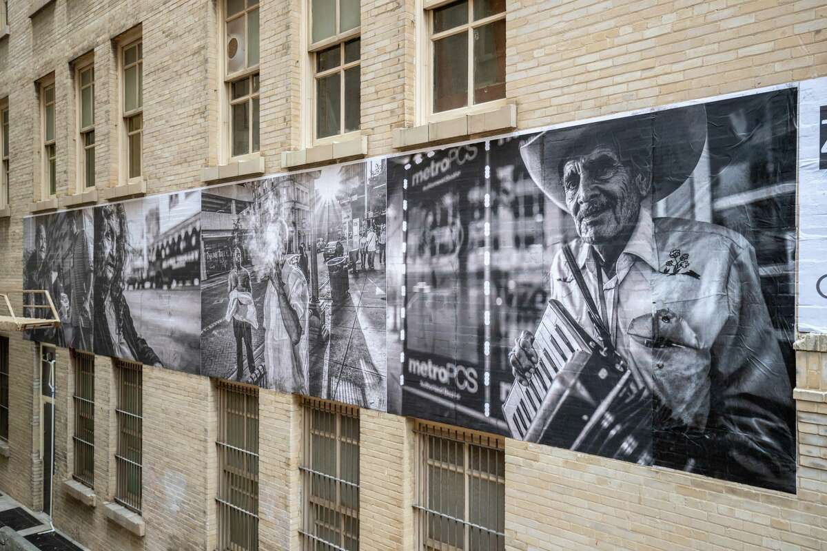 """Some of the portraits published in the 2018 book """"Humans of San Antonio"""" now cover an exterior wall of the 118 Broadway building, looking over Peacock Alley. The wheat paste mural, which was installed over the weekend, is the largest in downtown."""