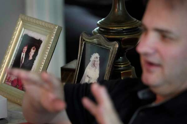 Steve Perkins is seeking answers to questions about his wife Ann's final moments. The framed photos show the couple taken in the 1990s and one of Ann on their wedding day in 1989.