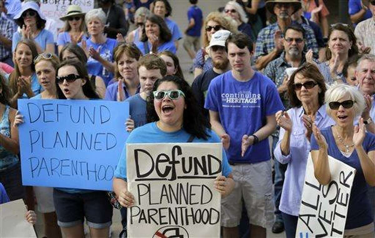 FILE- In this July 28, 2015 file photo, Erica Canaut, center, cheers as she and other anti-abortion activists rally on the steps of the Texas Capitol in Austin, Texas to condemn the use in medical research of tissue samples obtained from aborted fetuses. Planned Parenthood Federation of America held a conference call Thursday, Aug. 27, 2015, to discuss what it calls a â??smear campaignâ? against the organization and its affiliates by a California-based anti-abortion group. (AP Photo/Eric Gay, File)