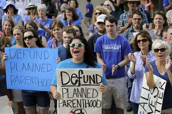 FILE- In this July 28, 2015 file photo, Erica Canaut, center, cheers as she and other anti-abortion activists rally on the steps of the Texas Capitol in Austin, Texas to condemn the use in medical research of tissue samples obtained from aborted fetuses. Planned Parenthood Federation of America held a conference call Thursday, Aug. 27, 2015, to discuss what it calls a â??smear campaignâ? against the organization and its affiliates by a California-based anti-abortion group. (AP Photo/Eric Gay, File)