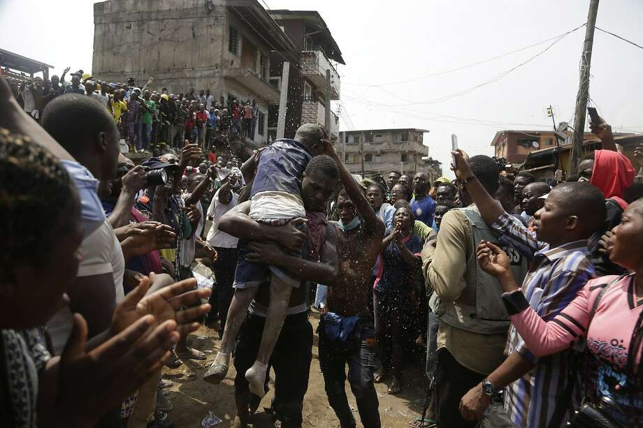 A child is rescued from the rubble of a three-story school building in Lagos, which collapsed while classes were in session. Photo: Sunday Alamba / Associated Press