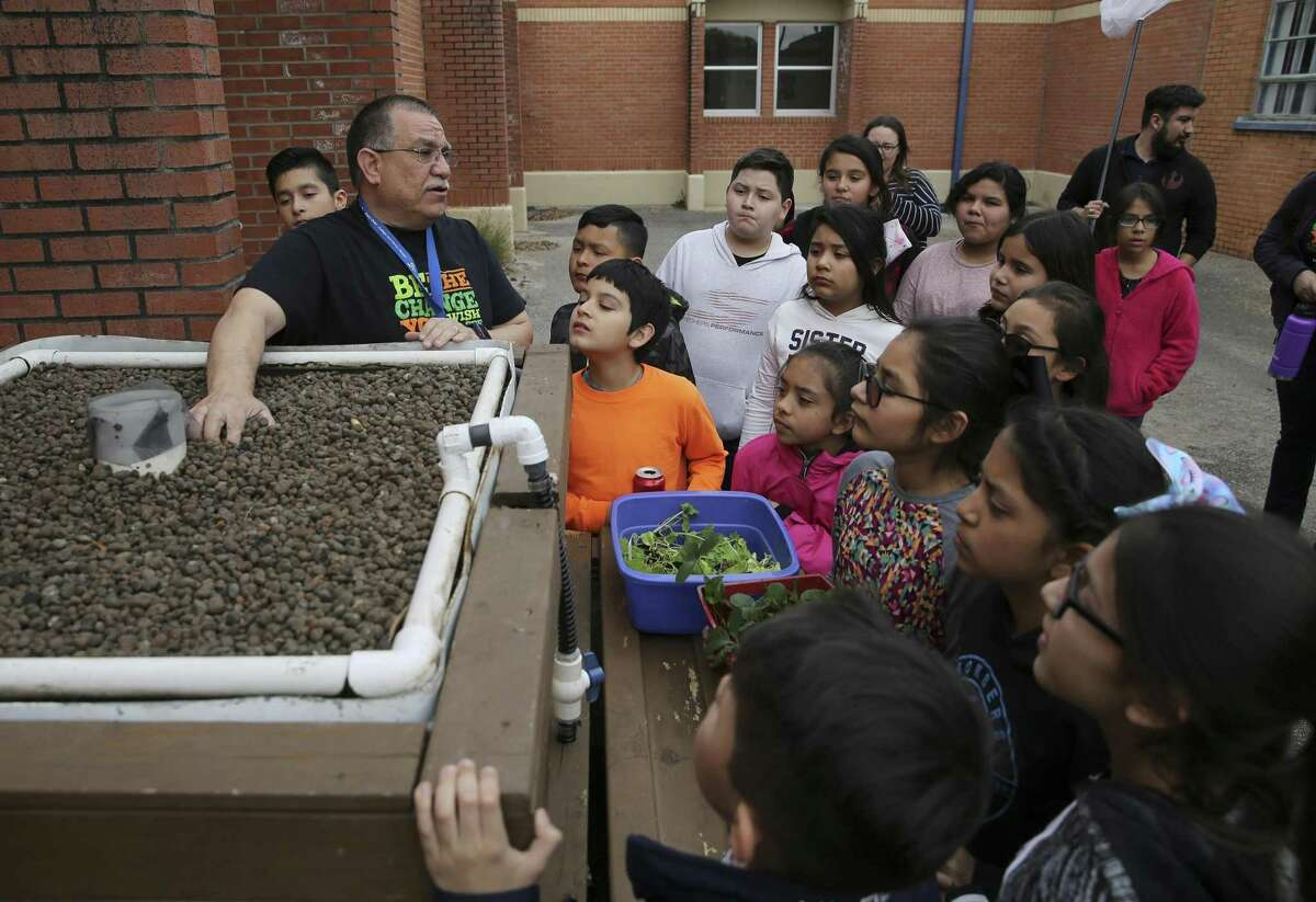 Teacher Miguel Quintanilla talks about an aquaponic garden before students put plants in it at Price Elementary on March 6, 2019.