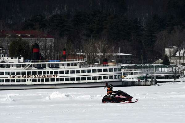 A snowmobile riders zips across the frozen surface of Lake George for some mid-week recreation on Wednesday, March 13, 2019, in Lake George, N.Y. (Will Waldron/Times Union)