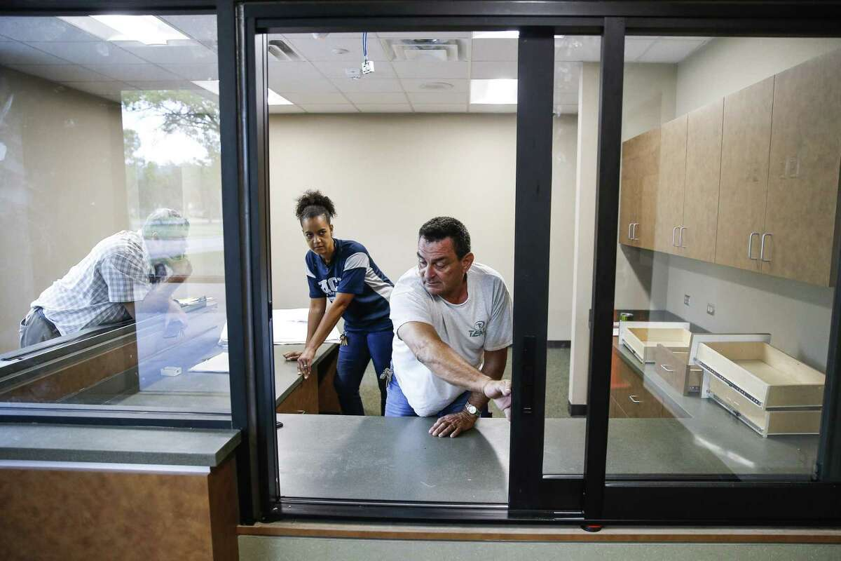 Alief ISD facilities project manager Glenn Jarrett, left, and Albright Middle School principal Lori Wyatt, center, watch as Teal Construction superintendent Jim Jones shows off the sliding door to greet visitors at the school's new security vestibule Tuesday Aug. 14, 2018 in Houston. The vestibule lets staff to interact with visitors before allowing them access to the building and also has a 911 call button.