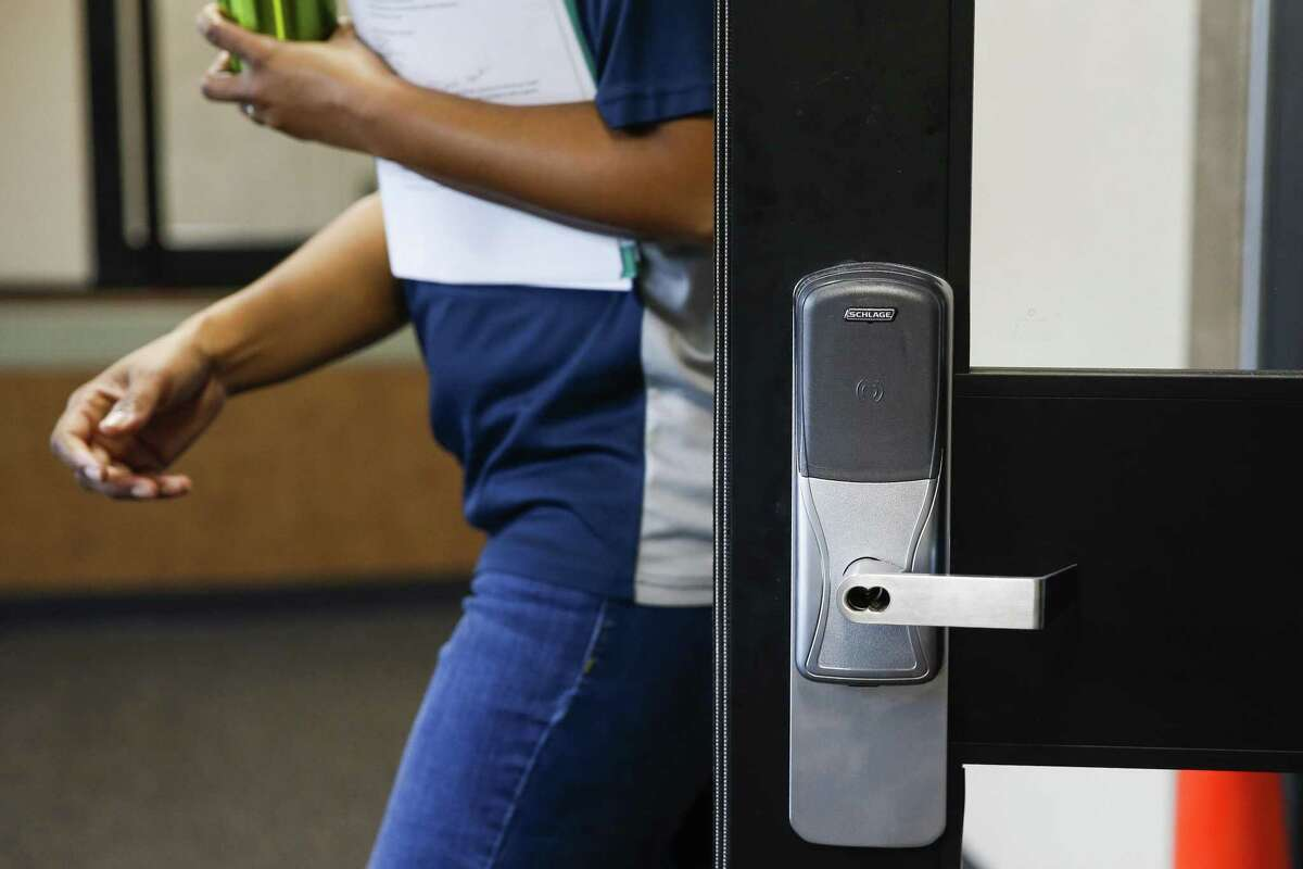 Albright Middle School principal Lori Wyatt walks next to an automatic lock outside a new security vestibule that has been added at the school Tuesday Aug. 14, 2018 in Houston. The vestibule lets staff to interact with visitors before allowing them access to the building and also has a 911 call button.