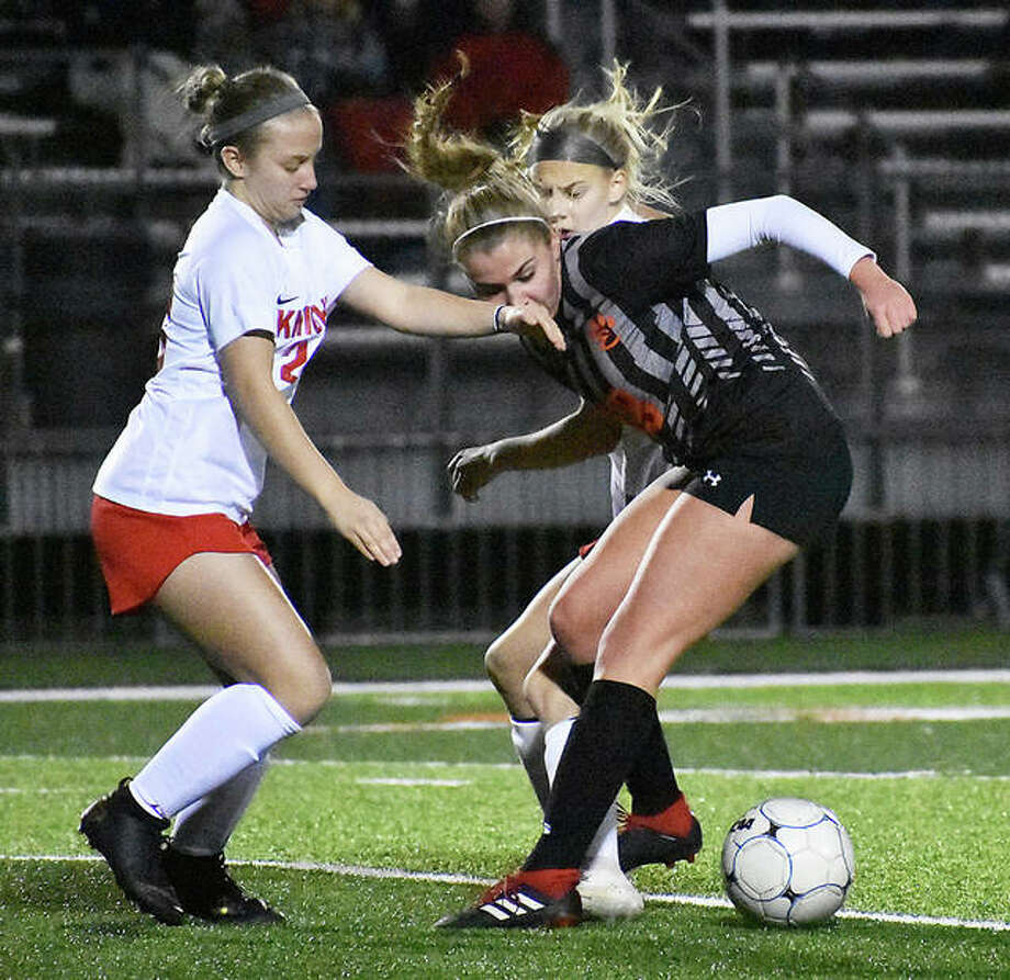 Edwardsville midfielder Zoe Ahlers tries to win the ball from two Triad players during the first half Tuesday inside the District 7 Sports Complex. Photo: Matt Kamp/The Intelligencer
