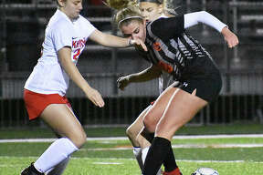Edwardsville midfielder Zoe Ahlers tries to win the ball from two Triad players during the first half Tuesday inside the District 7 Sports Complex.