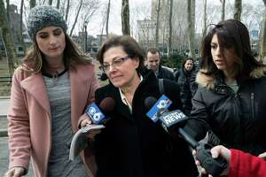 Nancy Salzman, center, is surrounded by reporters as she arrives at Brooklyn federal court, Wednesday, March 13, 2019, in New York. Salzman, a co-founder of NXIVM, an embattled upstate New York self-help organization, is expected to plead guilty in a case featuring sensational claims that some followers became branded sex slaves.