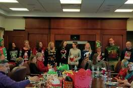 Employees of law firm Jackson Lewis' Albany office show off their ugly Christmas sweaters at an office holiday party.