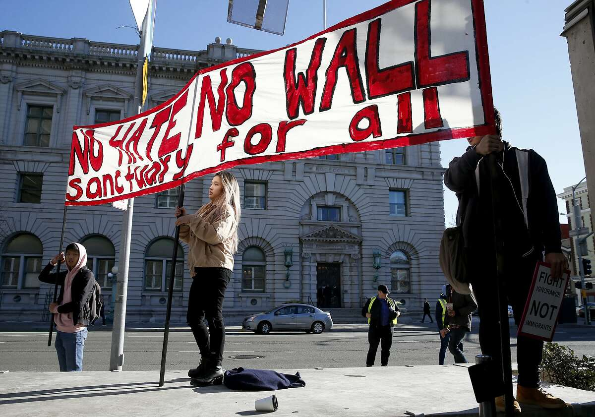 Protesters display a banner across the street from the James R. Browning United States Courthouse where the 9th Circuit Court of appeals are hearing arguments in President Trump's lawsuit against California's sanctuary law that protects immigrants in San Francisco, Calif. on Wednesday, March 13, 2019.