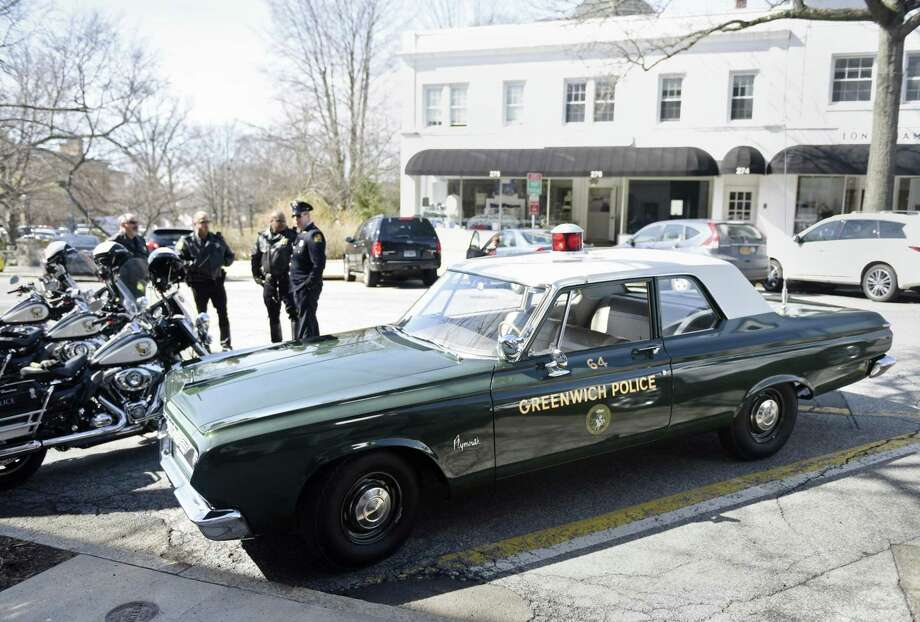 Greenwich Police officers gather around a1964 Plymouth Savoy police car replica, featuring a vintage light, siren, radio and spotlight, parked on Greenwich Avenue in Greenwich, Conn. Wednesday, March 13, 2019. The old police car led a procession for the funeral of Officer Michael Cofone, a Greenwich police officer from 1948 to 1973. At 97, Officer Cofone was the oldest retiree of the Greenwich Police Department. During his tenure as an officer, Cofone helped rescue a man trapped in the Pickwick Arms Hotel during a fire and performed CPR on another town resident, saving his life, according to the department. Photo: Tyler Sizemore / Hearst Connecticut Media / Greenwich Time