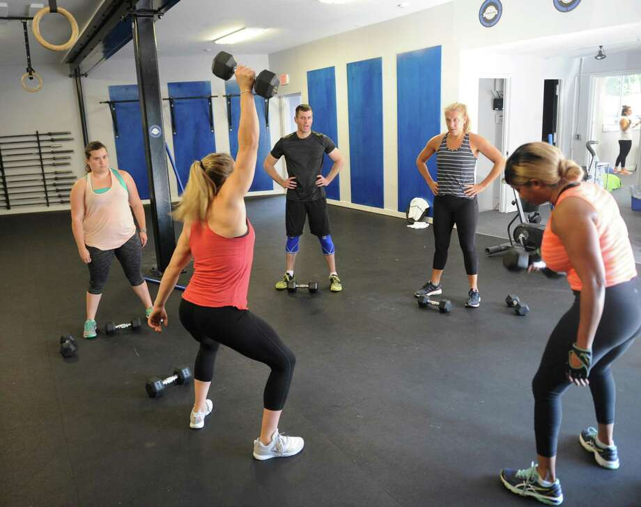 A fitness instructor leads a class at Old Greenwich Fitness Club & CrossFit in Old Greenwich, Conn., among more than 80 venues in Connecticut that now accept ClassPass members to their facilities and classes. Photo: Tyler Sizemore / Hearst Connecticut Media / Greenwich Time