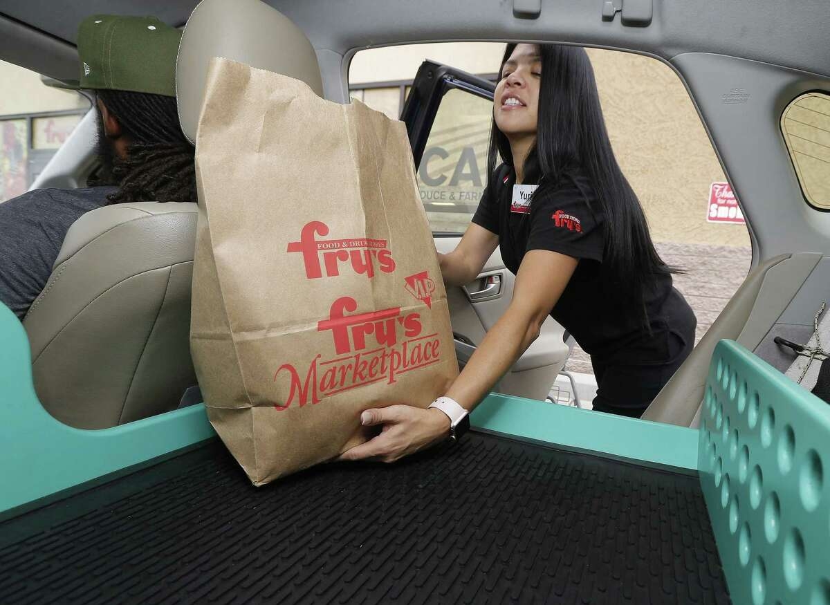 Fry's customer service representative Yuri Alvarado puts groceries into the self-driving Nuro vehicle parked outside a Fry's supermarket, which is owned by Kroger, as part of a pilot program for grocery deliveries on Aug. 16, 2018, in Scottsdale, Ariz. Kroger announced Wednesday it would start automated deliveries at two stores in Houston.