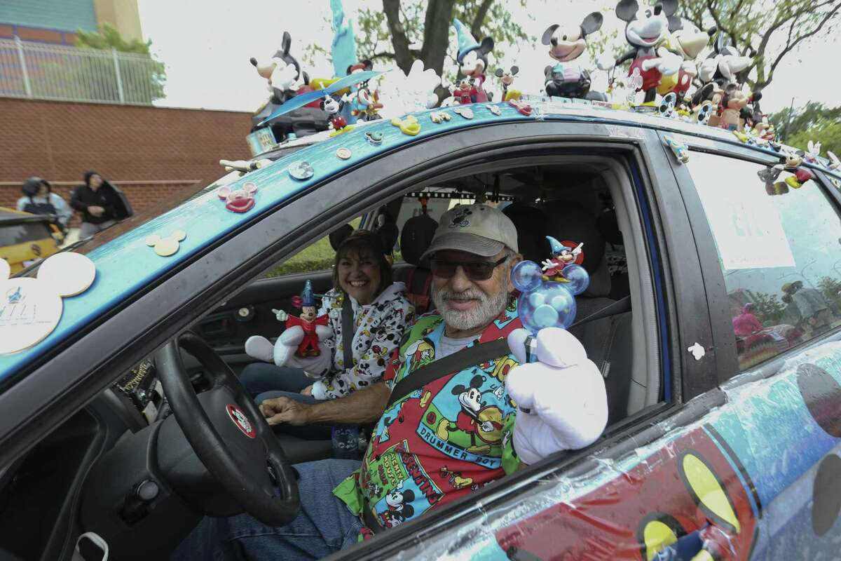 """Debbie and Mike Dellinger, of Dallas, drive their """"Michkia Mouse,"""" because it is a KIA, art car to participate the 31st Annual Houston Art Car Parade on Allen Parkway on Saturday, April 14, 2018, in Houston. Debbie has been collecting Mickey mouse for decades and they just built the car in March. More than 250 art cars participated in this year's parade. ( Yi-Chin Lee / Houston Chronicle )"""