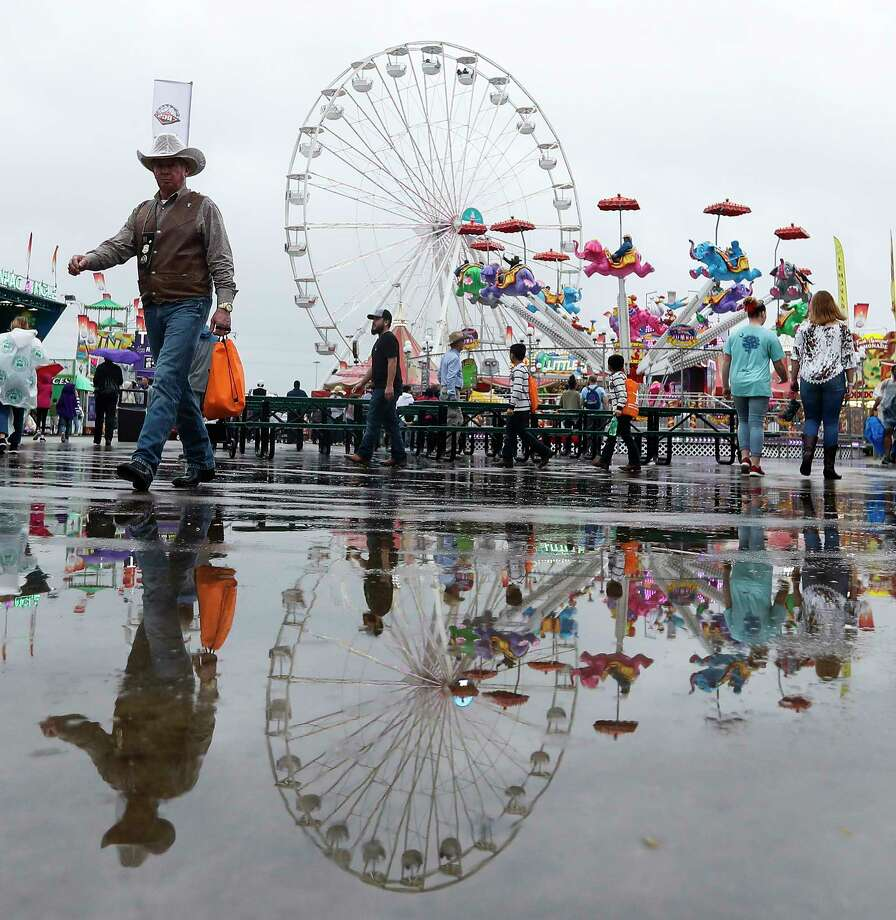 Rodeo-goers reflected in a puddle in the kids carnival area during the Houston Livestock Show and Rodeo at NRG Park, Wednesday, March 13, 2019, in Houston. Photo: Karen Warren, Staff Photographer / © 2019 Houston Chronicle