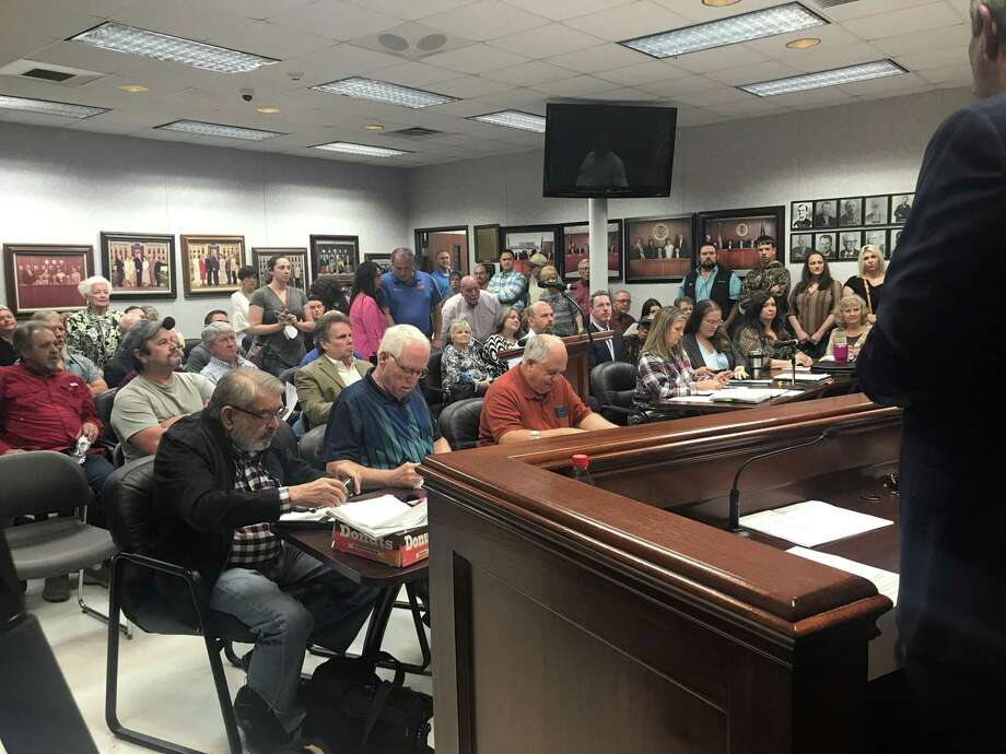 The crowd at Wednesday's Commissioner's Court meeting in Orange County spilled out into the surrounded hallways. To the surprise of the court, County Judge Dean Crooks announced he would resign, effective next week. Photo: Kaitlin Bain / Beaumont Enterprise