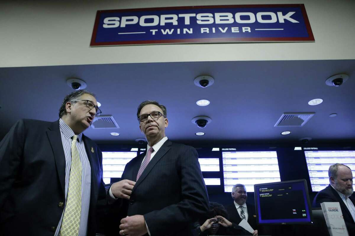 Twin River Casino Hotel Vice President and General Manager Craig Sculos, left, and John Taylor, chairman of Twin River Worldwide Holdings, second from left, prepare to face reporters before a ceremony on the first day of sports betting, Monday, Nov. 26, 2018, at Twin River Casino Hotel, in Lincoln, R.I. Rhode Island is the first New England state to legalize sports betting since the U.S. Supreme Court struck down a federal law this year that made most sports gambling illegal. (AP Photo/Steven Senne)