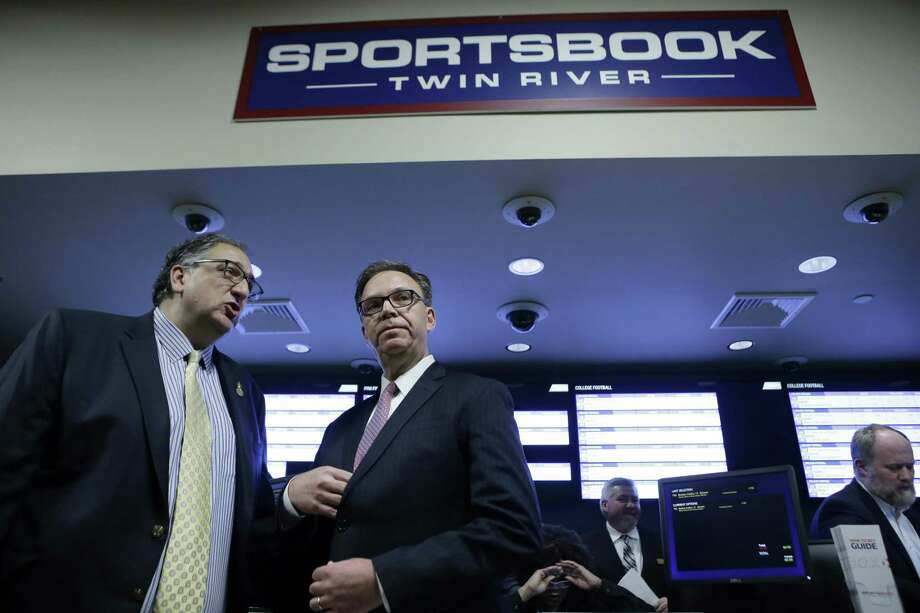 Twin River Casino Hotel Vice President and General Manager Craig Sculos, left, and John Taylor, chairman of Twin River Worldwide Holdings, second from left, prepare to face reporters before a ceremony on the first day of sports betting, Monday, Nov. 26, 2018, at Twin River Casino Hotel, in Lincoln, R.I. Rhode Island is the first New England state to legalize sports betting since the U.S. Supreme Court struck down a federal law this year that made most sports gambling illegal. (AP Photo/Steven Senne) Photo: Steven Senne / Associated Press / Copyright 2018 The Associated Press. All rights reserved