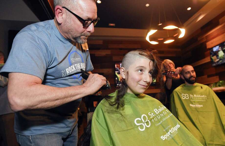 Above, Bill Forcier, of Choppers Salon, shaves the head of Michael Ricci, of Greenwich, during the 2019 Rock the Bald event at Bobby V's Restaurant & Sports Bar in Stamford on Wednesday. At left, Lisa Henderson, an employee of OdysseyRe, holds up her hair that hair stylist Wayne DeVingo preserved for her as he shaved her head. Ricci and Henderson were among 40 participants from seven Stamford-based corporations to have their heads shaven, raising over $150,000 dollars for the St. Baldrick's Foundation to fund innovative research programs to help fight childhood cancers. Photo: Matthew Brown / Hearst Connecticut Media / Stamford Advocate