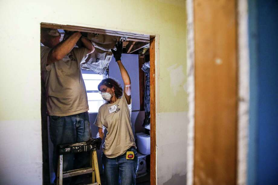 Eight Days of Hope volunteers Max and Donna Zollers work to hang insulation in the bathroom of a home flooded by Hurricane Harvey Saturday, March 10, 2018 in Dickinson. Thousands of volunteers spread out across the Houston area to help more than 500 homeowners repair or rebuild their homes in the wake of the hurricane. (Michael Ciaglo / Houston Chronicle) Photo: Michael Ciaglo, Staff Photographer / Houston Chronicle / Michael Ciaglo