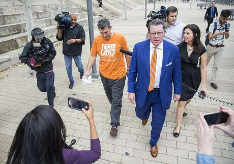 University of Texas men's tennis coach Michael Center, left, is accused of accepting roughly $100,000 in bribes.