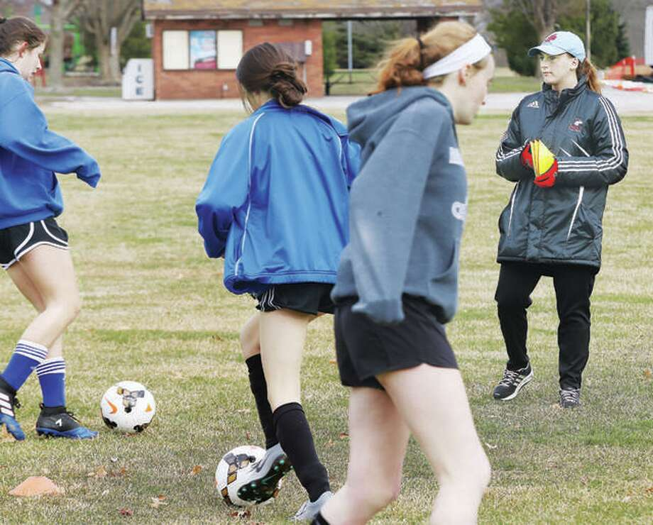 First-year Alton High girls soccer coach Gwen Sabo, far right, keeps on eye on a Marquette Catholic High practice last spring. Sabo, former Alton and Northern Illinois player and a former Telegraph Player of the Year, was an assistant at Marquette last year. Photo: Telegraph File Photo
