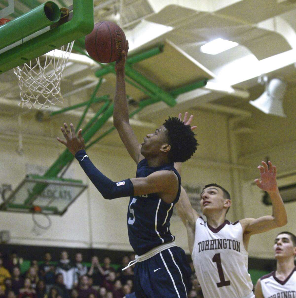 Amistad's Jaden Ratiff (5) goes past Torrington's Nick Balducci (1) to the basket in the CIAC Division III boys basketball semifinal game between Amistad and Torrington high schools, Wednesday, March 13, 2019, at Wilby High School, Waterbury, Conn.