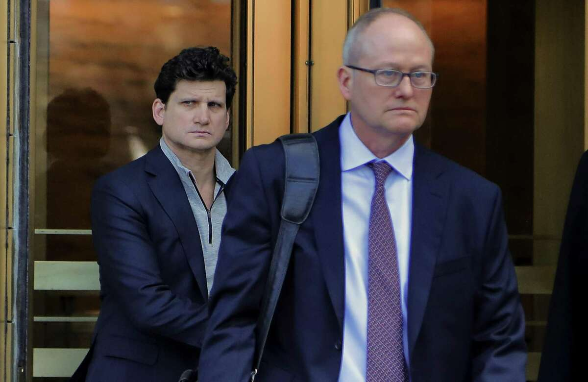 Gordon Caplan of Greenwich, left, walks out of federal court on Tuesday in New York. Caplan was accused of paying $75,000 to get a test supervisor to correct the answers on his daughter's ACT exam after she took it.