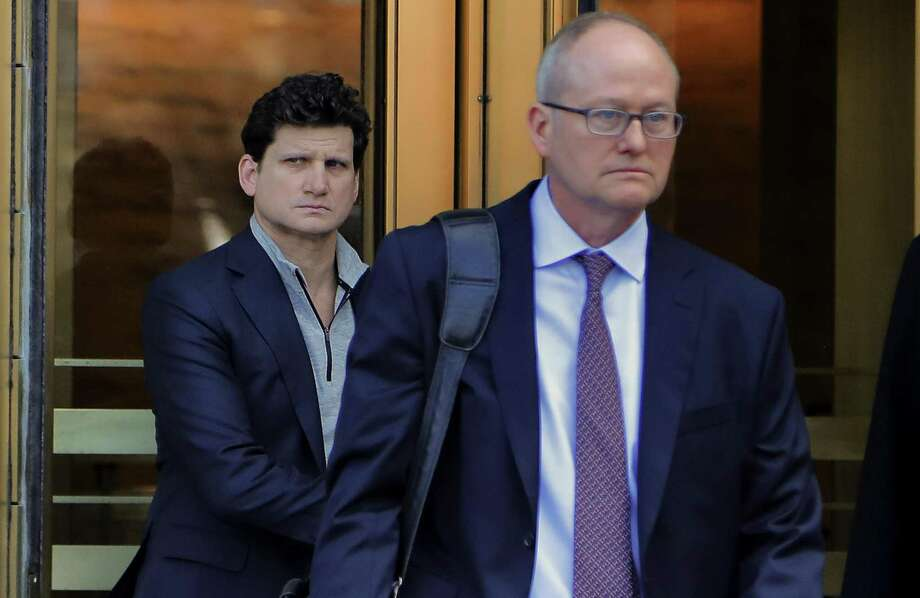 Gordon Caplan of Greenwich, left, walks out of federal court on Tuesday in New York. Caplan was accused of paying $75,000 to get a test supervisor to correct the answers on his daughter's ACT exam after she took it. Photo: Julie Jacobson / Associated Press / Copyright 2019 The Associated Press. All rights reserved
