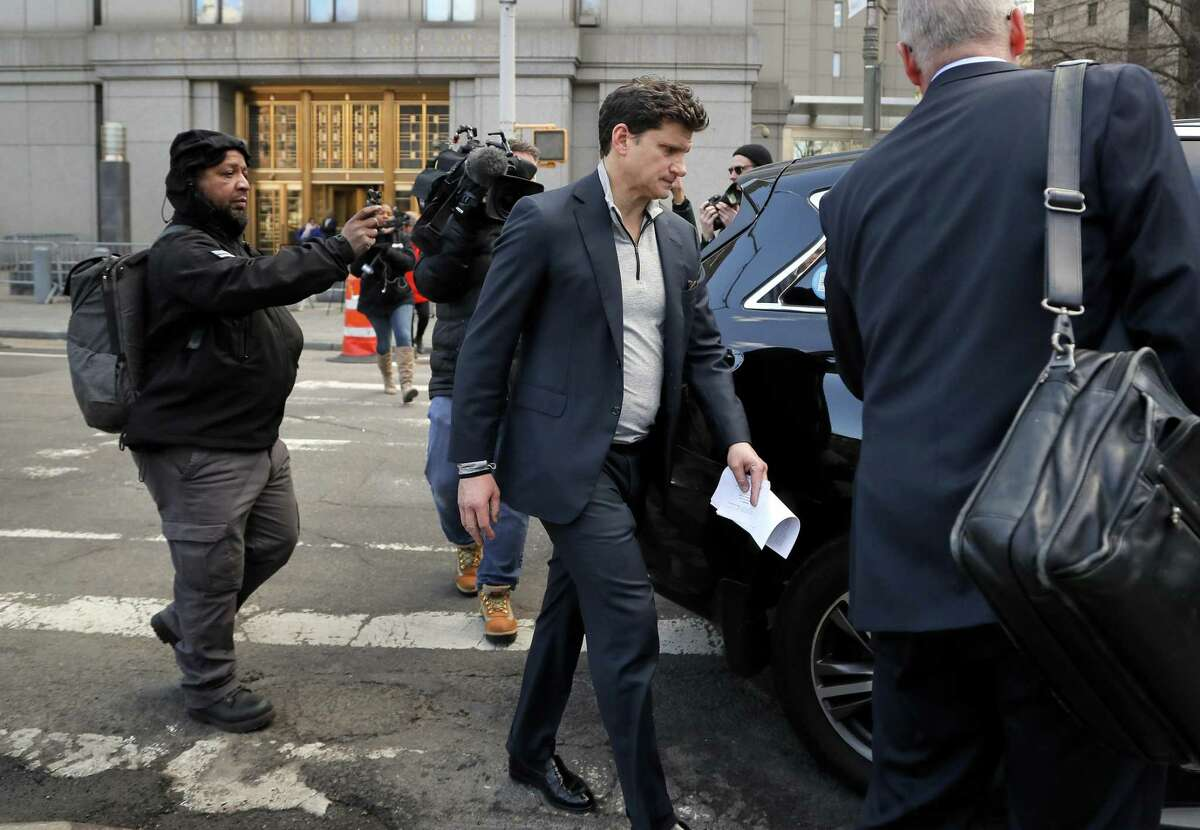 Gordon Caplan of Greenwich, center, walks out of federal court in New York City on Tuesday. Fifty people, including Hollywood stars Felicity Huffman and Lori Loughlin, were charged in a admissions bribery scheme. in which wealthy parents allegedly bribed college coaches and other insiders to get their children into some of the nation's most selective schools. Caplan, who is co-chairman of the international law firm Willkie Farr & Gallagher, was accused of paying $75,000 to get a test supervisor to correct the answers on his daughter's ACT exam after she took it. (AP Photo/Julie Jacobson)
